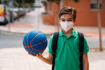 Boy wearing mask with a basketball to play on the street in the pandemic