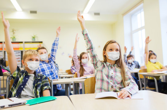 education, pandemic and health concept - group of students wearing face protective medical mask for protection from virus disease raising hands at school