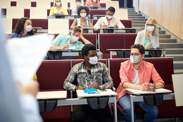 education, pandemic and health concept - group of international students wearing face protective medical mask for protection from virus disease at lecture hall