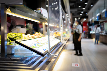Food shop in a mall have a plastic shield partition between customers with salespeople or food sellers in the food court,plastic shield as a barrier to prevention of infection social distancing safety