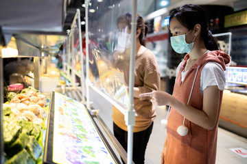 Asian child girl in a protective mask,ordering food in food court at the department store after Coronavirus quarantine Covid-19 with plastic shield partition,social distancing safety,new normal life