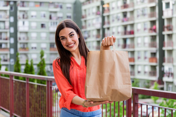 Woman Doing Shopping For Senior Neighbors. Young beautiful woman holding take away paper bag from...