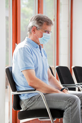Visitor or patient sitting in an empty waiting room with face mask because of coronavirus