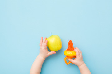 Infant hands holding green apple and orange baby nibbler on light blue table background. Chewing fresh fruit through net sack of feeder. Pastel color. Closeup. Top down view.