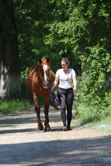 Girl walks with a horse through the wood