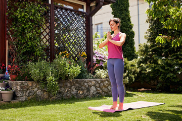 Young attractive brunette standing on the mat in her backyard in sun salutation position.