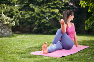 Young gorgeous brunette sitting on the mat in her backyard in Sage Marichi's III yoga posture.