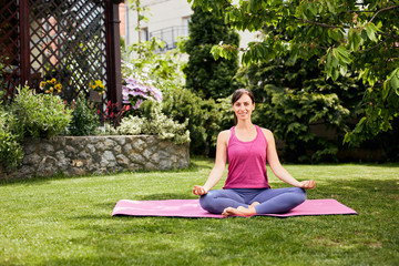 Young attractive brunette sitting in her backyard in lotus position and meditating.