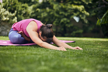 Young flexible caucasian yogi brunette sitting on the mat in her backyard in lotus posture with arms extended.