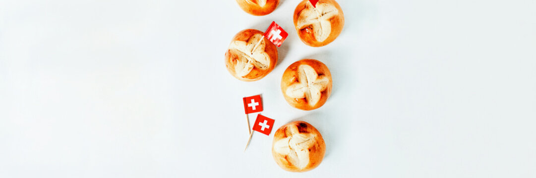 Swiss bread buns baked in Switzerland to celebrate Swiss National Day on August 1st. Long web banner, white background.