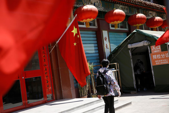 Woman walks outside a TCM hospital decorated with a Chinese flag in Beijing