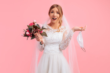 bride in a wedding dress with a medical protective mask in her hands, on a pink background. Quarantine, wedding, coronavirus Wall mural