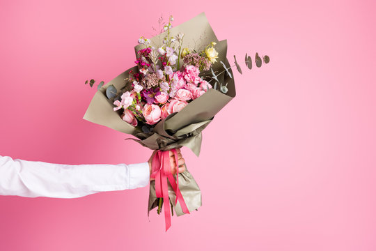 Photo of cropped man arm hold big bright decorated bunch giving girlfriend valentine day romance gift present bouquet composition isolated pink color background