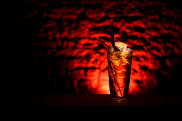 glass of cold drinks with glassy straw for drinking stands on bar