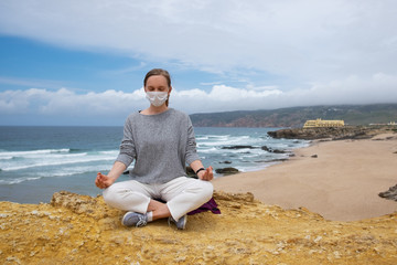 Peaceful woman wearing face mask, meditating in lotus pose, keeping arms in zen gesture. Front view. Stress relief during outbreak concept