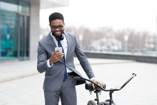 Handsome business man texting on phone holding his bike