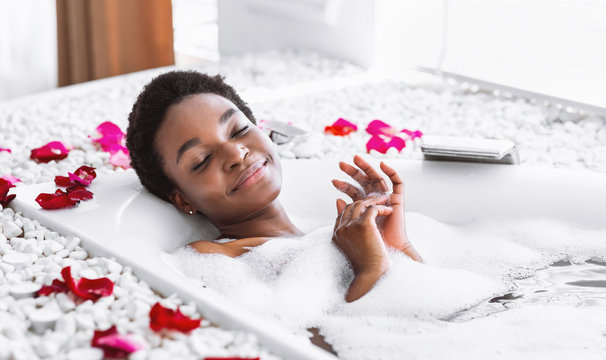 African american woman takes bath with foam and petals