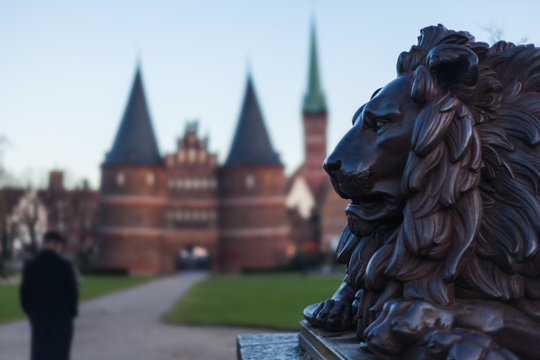Holstentor in Lübeck with lion statue in the foreground UNESCO World Heritage Site landmark Gothic style historic cityscape ornaments restored brick Petrikirche big cat