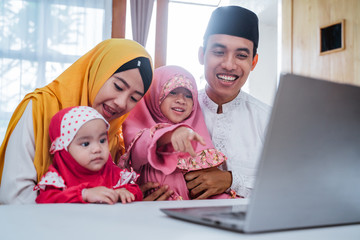 muslim family video confrence with other using laptop on eid mubarak celebration