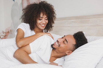 Young calm african loving couple girl guy in t-shirts lying on bed with white sheet pillow blanket...