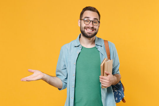 Smirked smiling young man student in casual clothes glasses backpack hold books isolated on yellow background studio portrait. Education in high school university college concept. Spreading hands.