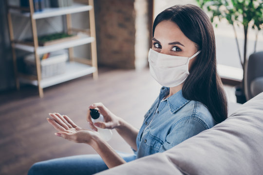 Close-up portrait of her she nice attractive brunette girl sitting on divan wearing safety mask using disinfection spray in modern loft industrial house flat apartment safe place indoors