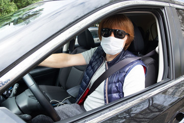 Male car driver wearing sunglasses and medical mask, protecting face during coronavirus outbreak. Vehicle side window. Car driver and virus pandemic concept