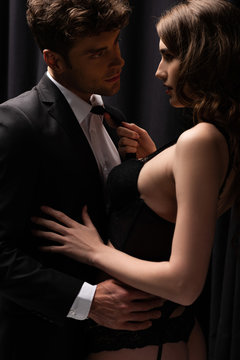 seductive woman pulling tie of handsome man in suit on black