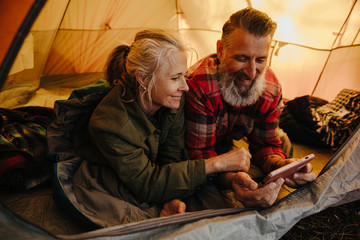 Happy senior couple using phone inside tent on camping trip