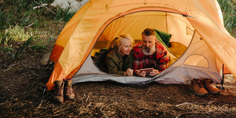 Caucasian elderly couple browsing on phone while laying in bedroll in tent