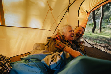 Senior couple laughing and cuddling inside tent in bedroll