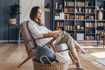 Business woman sitting in a chair at home