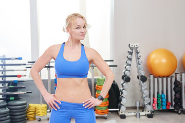 Sexy adult woman with muscular body posing with dumbbells on the background of the gym. Fitness exercises, sportswear and sports nutrition