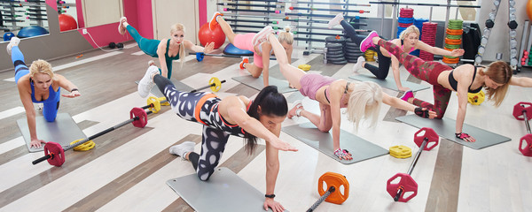 Fitness workout in the gym. Group of women doing plank, exercises for abdominal muscles in colorful sportswear