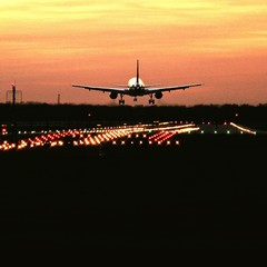 Tuinposter Airplane Flying Above Airport Runway During Sunset