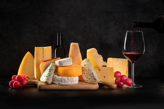 Cheese, many different types with grapes and pouring wine, side view on a black background with a place for text