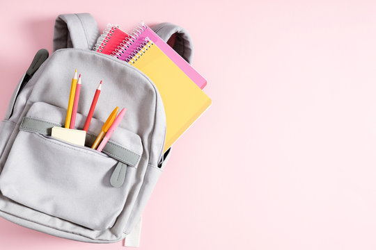 Back to school concept. Backpack with school supplies, pens, pencils, notebook on pastel pink background. Flat lay, top view, copy space