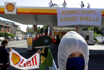 Environmental activists hold up banners in at a Shell petrol station in Prague