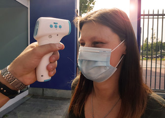 coronavirus woman whose fever is measured with digital thermometer at the entrance of an outdoor place