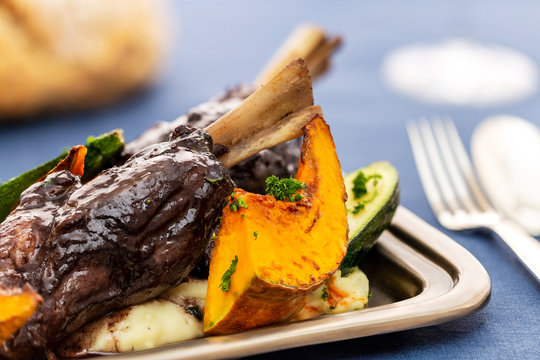 Glazed braised lamb shank on potato puree with large pumpkin and zucchini pieces in a silver tray on a blue cloth.