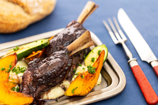 Glazed braised lamb shank on potato puree with large pieces of pumpkin and zucchini on a silver tray on a blue tablecloth aside vintage silver serving utensils and bread loaf.