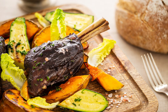 Glazed braised lamb shank with large pieces of pumpkin and zucchini on a cutting board with pink salt on a beige tablecloth aside a vintage silver fork and a bread loaf.