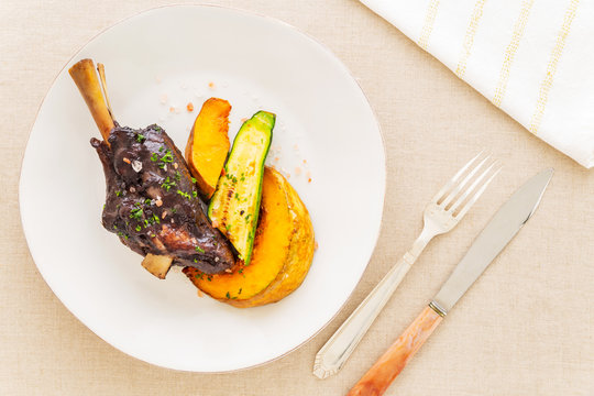 Glazed braised lamb shank with pumpkin and zucchini in a beige plate on a beige tablecloth aside a fork, a knife and a white napkin. Flat lay top view.