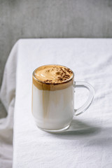 Dalgona frothy coffee trend korean drink milk latte with coffee foam in glass mug, decorated by ground coffee on white cotton table cloth.