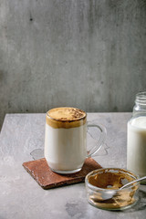 Dalgona frothy coffee trend korean drink milk latte with coffee foam in glass mug, decorated by ground coffee on gray texture table. Ingredients above