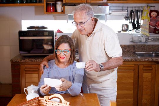 Coppia di anziani divertiti in cucina fanno una video chiamata con lo smartphone mentre fa colazione