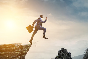 Black businessman jumping over mountain stones