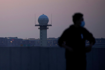 A man wearing a face mask is seen in front of a radar tower at Hongqiao International Airport in Shanghai