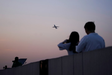 People watch a plane take off at Hongqiao International Airport in Shanghai