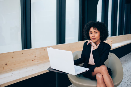Dark skinned female entrepreneur sitting indoors and looking at camera in break of working on laptop device, attractive woman waiting for business meeting and preparing for presentation via netbook
